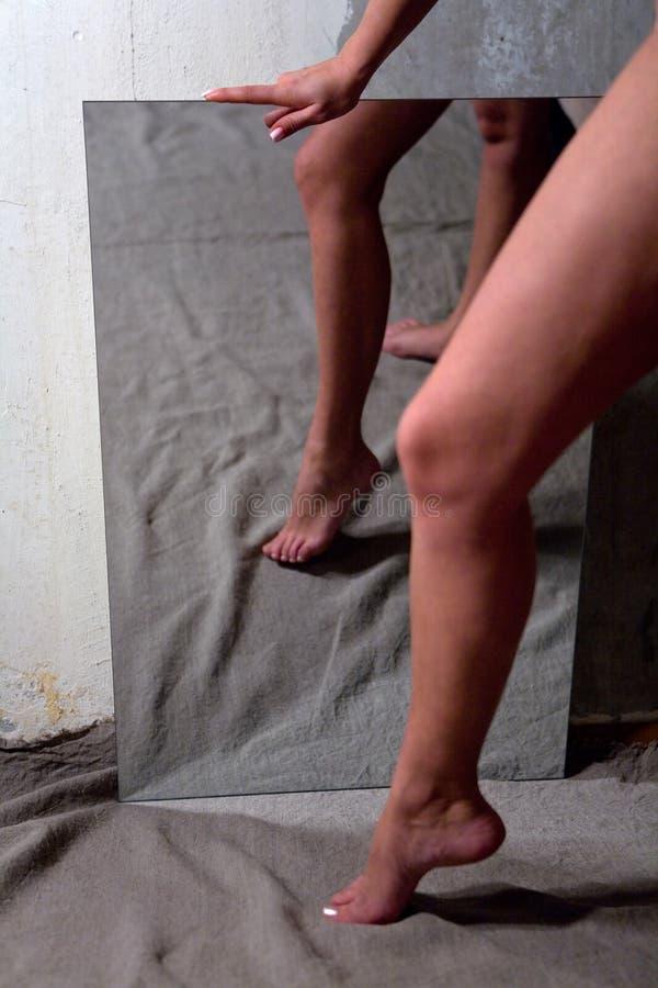 Belle jambe femelle nue mince et sa réflexion dans le miroir photographie stock libre de droits