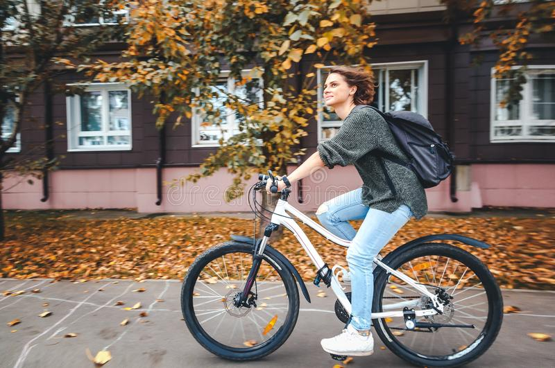 Belle jeune étudiante dans un chandail et des jeans sur un bicyc image libre de droits