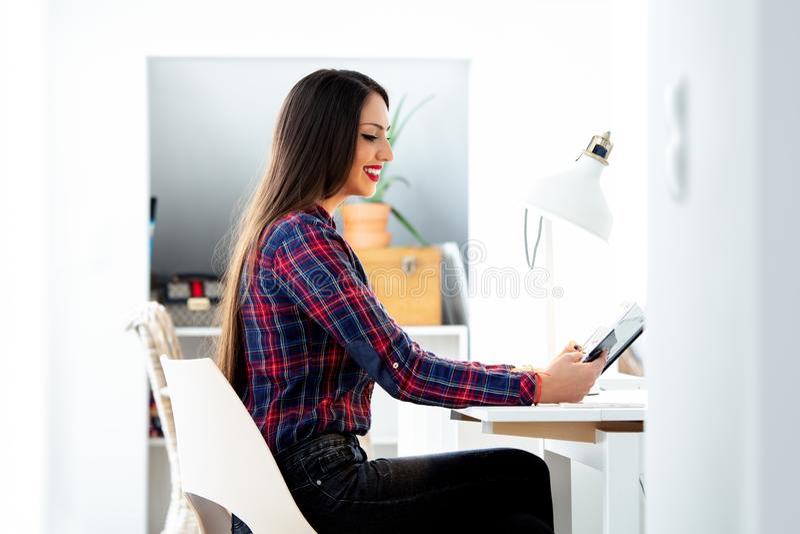 Belle jeune étudiante s'asseyant à son bureau, étudiant photo stock