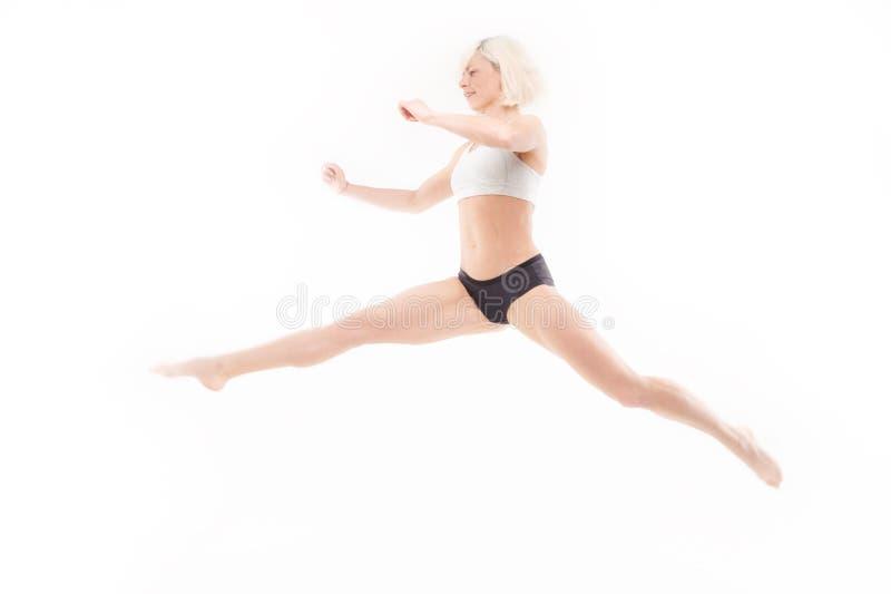 Belle jeune blonde dans un saut photographie stock