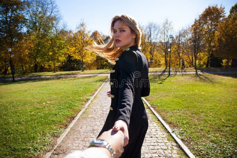 Belle jeune blonde et tenir la main de l'homme non identifié et marche avec lui sur le parc ensoleillé d'automne images libres de droits