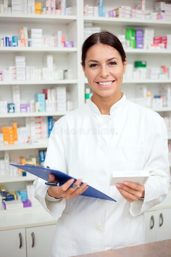 Belle jeune boîte de participation de pharmacien des médicaments et d'un presse-papiers photos stock