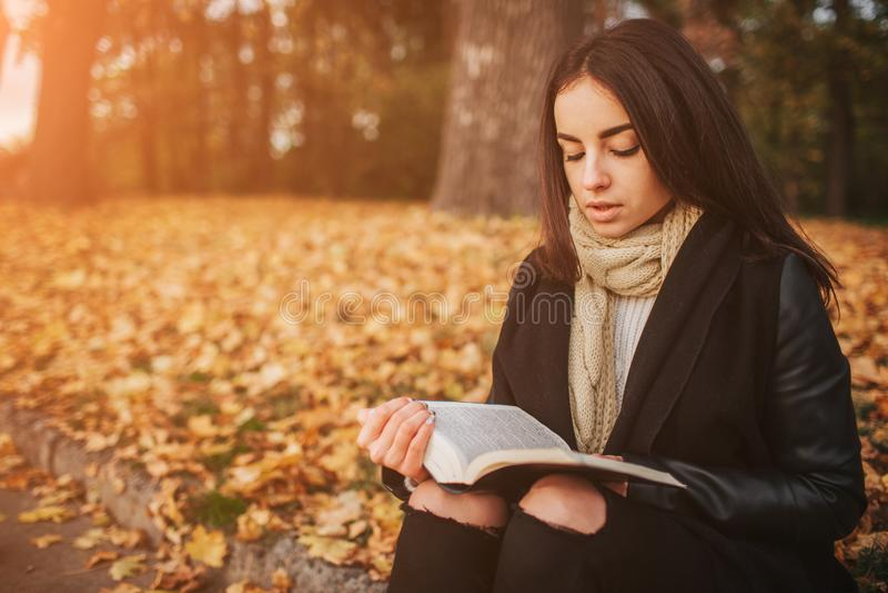 Belle jeune brune se reposant sur les feuilles d'automne tombées en parc, lisant un livre photo libre de droits