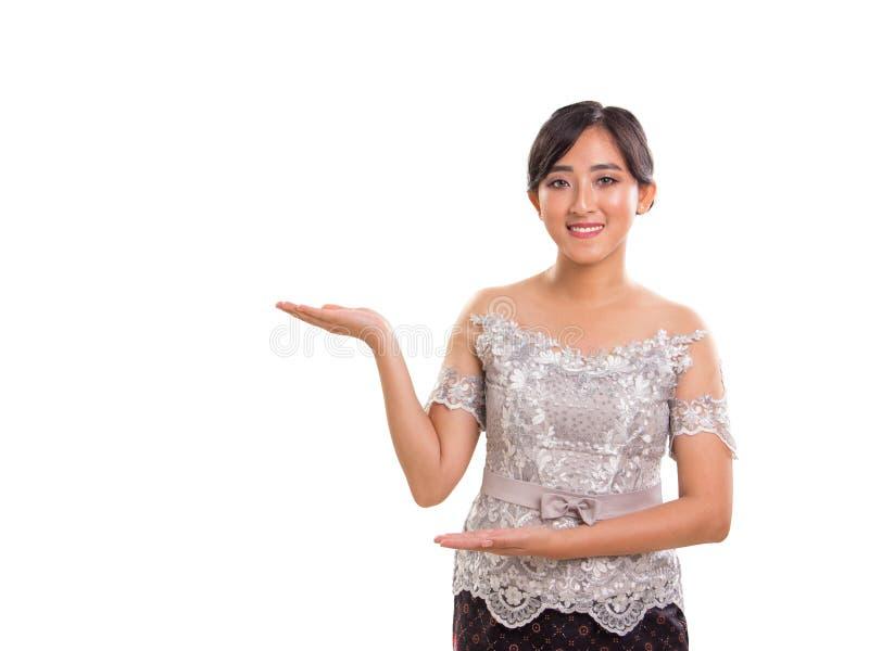 Belle jeune dame asiatique de Souteast faisant des gestes la promotion ou donnant s photos libres de droits