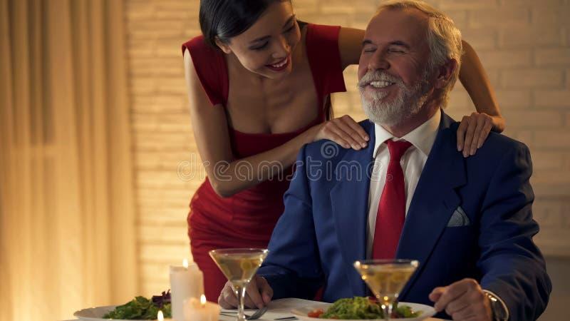 Belle jeune dame massant des épaules de vieil homme riche, flirtant la date image libre de droits