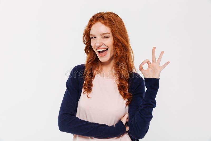Belle jeune dame rousse heureuse montrant le geste correct photographie stock