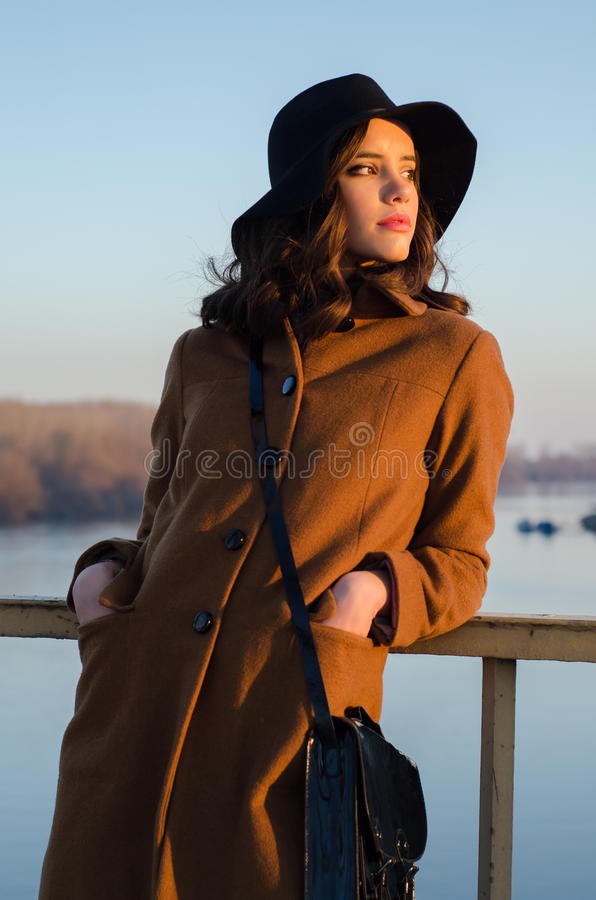 Belle jeune dame se tenant sur le coucher du soleil de observation d'automne de pont photographie stock libre de droits