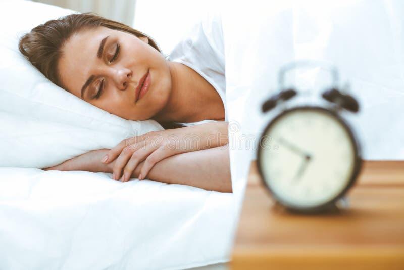 Belle jeune et heureuse femme dormant tout en se situant dans le lit confortablement et avec bonheur souriant photographie stock