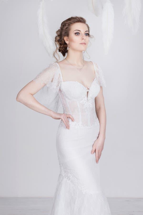 Belle jeune et rêveuse jeune mariée dans une robe de mariage luxueuse de dentelle photos libres de droits