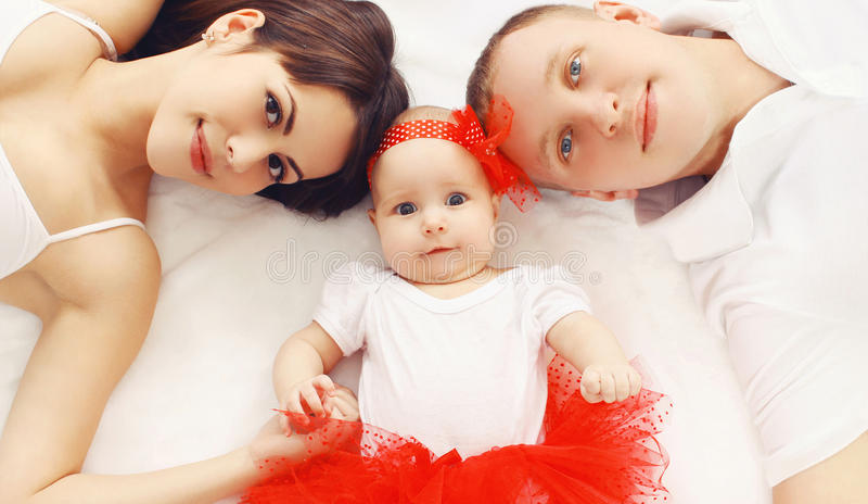 Belle jeune famille se trouvant ensemble sur le lit à la maison photographie stock libre de droits