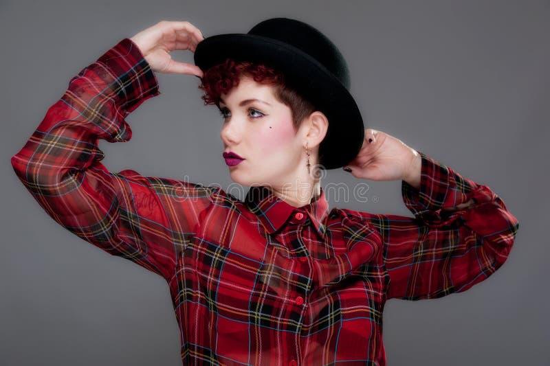 Belle jeune femelle dans le chapeau et la chemise de chapeau melon image stock
