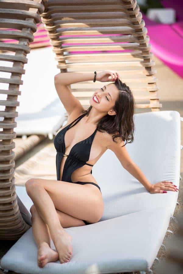 Belle jeune femelle dans un mensonge noir de bikini étayée sur ses mains sur un canapé en bois au lieu de villégiature luxueux photographie stock