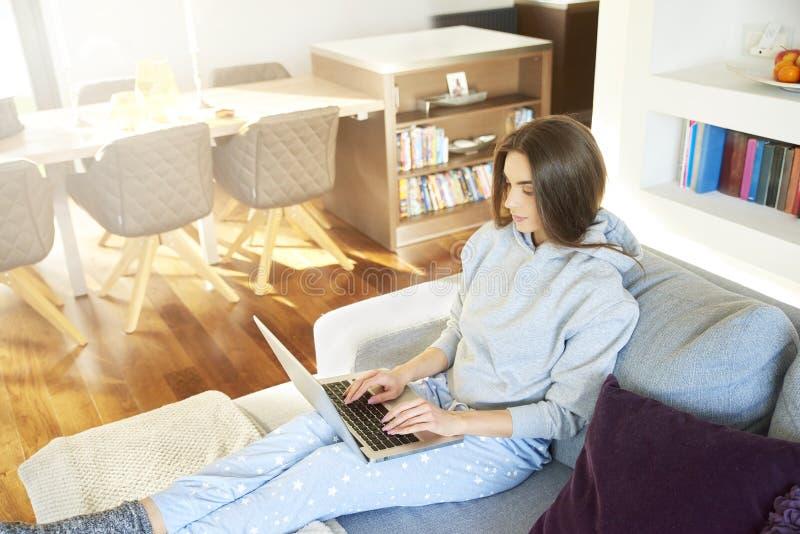 Belle jeune femme à l'aide de l'ordinateur portable tout en détendant à la maison images stock