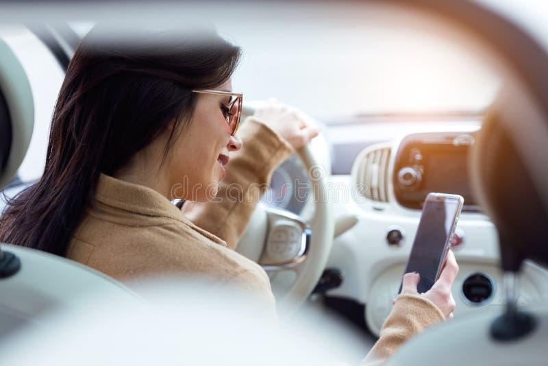 Belle jeune femme à l'aide de son téléphone portable dans la voiture images libres de droits