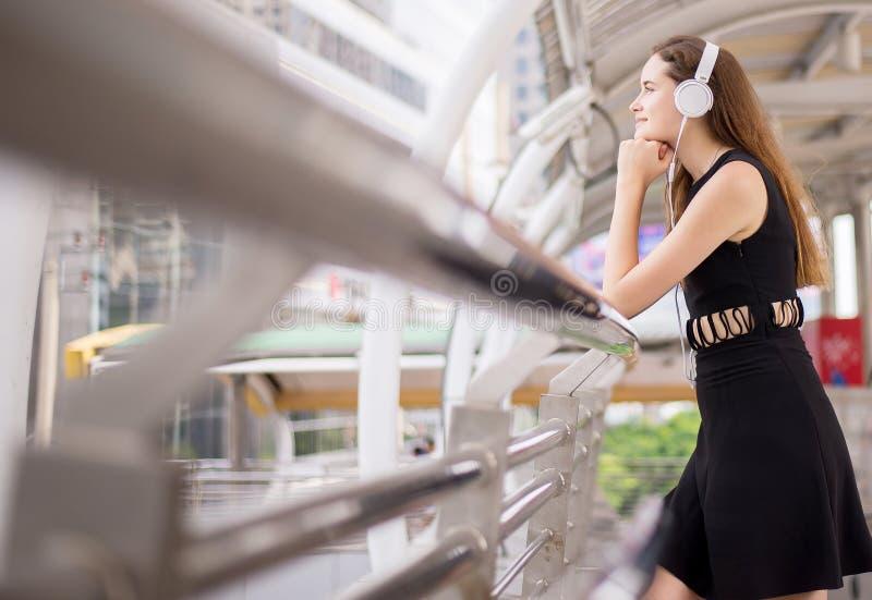 Belle jeune femme à l'aide des écouteurs et écoutant la musique dans la ville photos stock