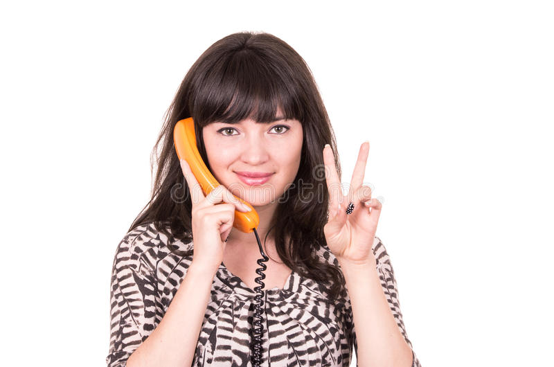 Belle jeune femme à l'aide du rétro téléphone orange photographie stock
