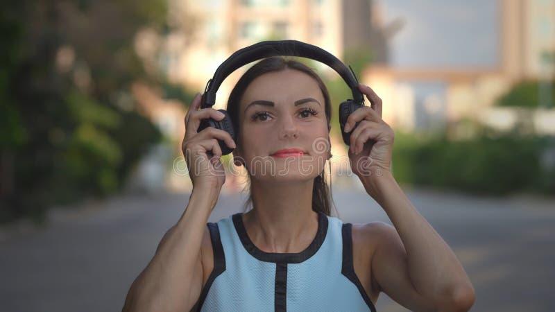 Belle jeune femme à l'aide du téléphone intelligent, messages de dactylographie, écoutant la musique, café potable tout en marcha photo libre de droits