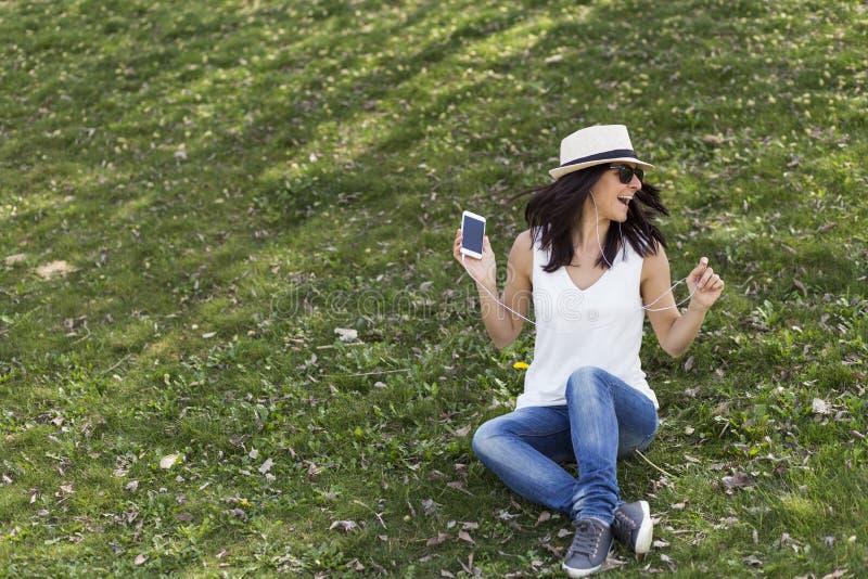 Belle jeune femme écoutant la musique à son téléphone intelligent elle image libre de droits