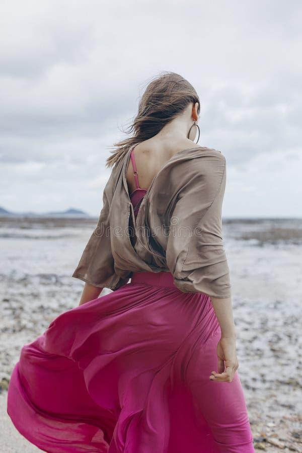 Belle jeune femme élégante dans la jupe rouge marchant sur la plage image libre de droits