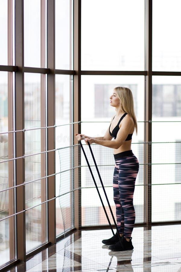 Belle jeune femme établissant dans un gymnase avec de grandes fenêtres avec la bande élastique Style de vie actif Sports dans le  photos stock