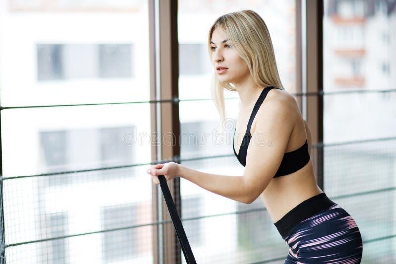 Belle jeune femme établissant dans un gymnase avec de grandes fenêtres avec la bande élastique Style de vie actif Sports dans le  photos libres de droits
