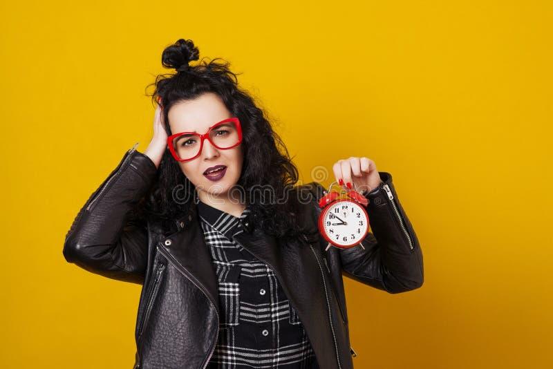 Belle jeune femme étonnée avec le réveil se tenant devant le fond jaune images stock