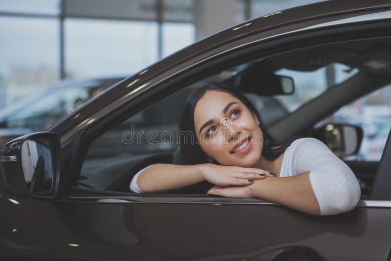 Belle jeune femme achetant la nouvelle voiture au concessionnaire images libres de droits