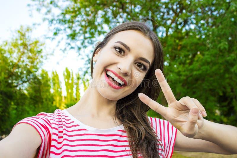 Belle jeune femme adulte prenant la photo d'elle-même, selfie photographie stock
