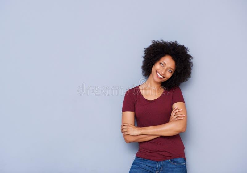 Belle jeune femme africaine se tenant sur le fond gris avec des bras croisés image libre de droits