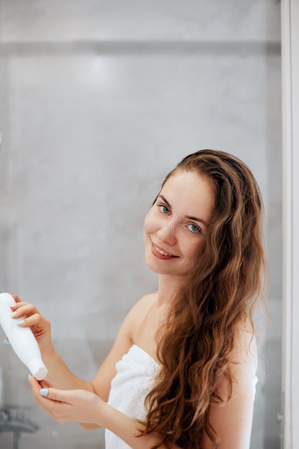 Belle jeune femme appliquant la lotion pour des cheveux et la position de sourire de moment devant le miroir image libre de droits