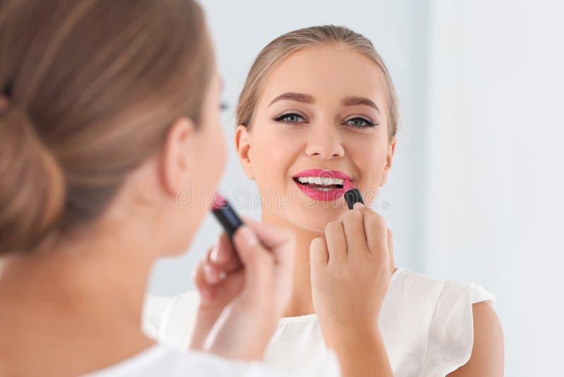 Belle jeune femme appliquant le rouge à lèvres dans le miroir images stock