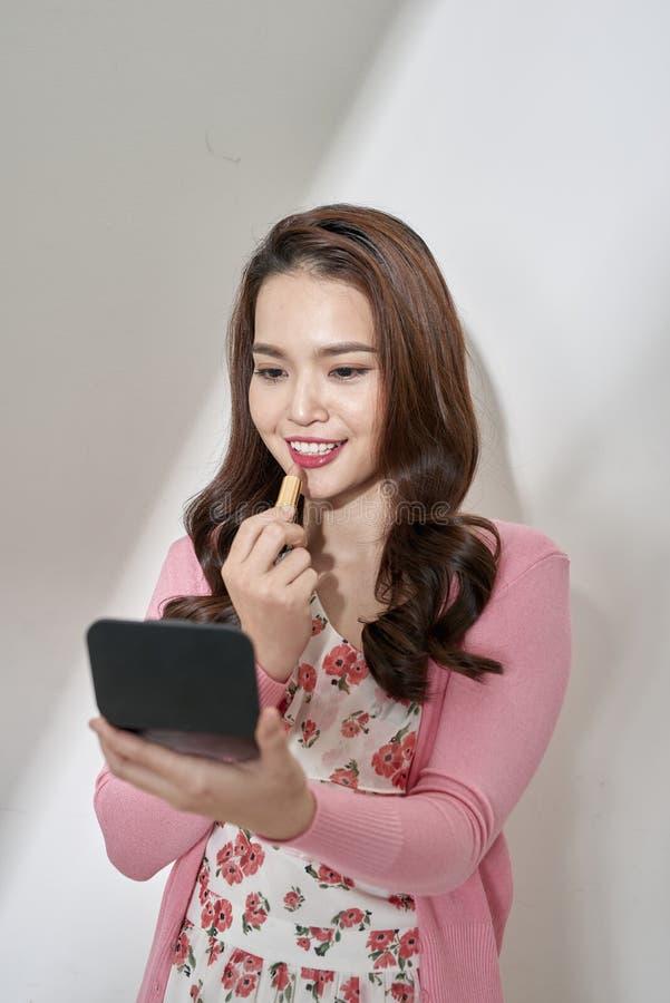 Belle jeune femme appliquant le rouge à lèvres rose, regardant dans le petit miroir image libre de droits