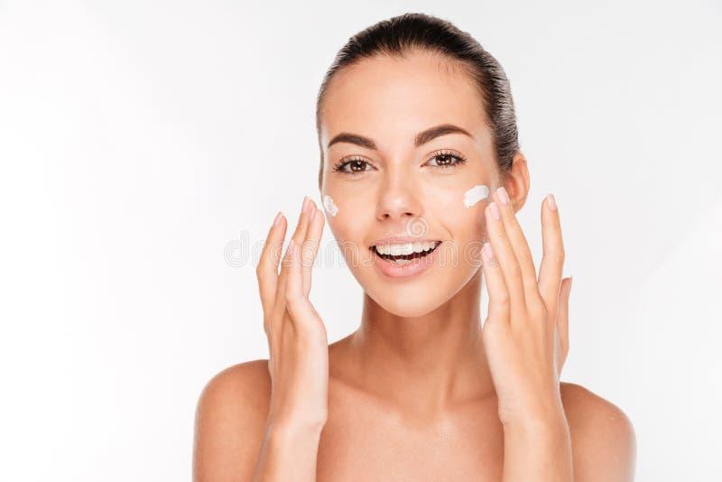 Belle jeune femme appliquant le traitement crème cosmétique sur son visage photo libre de droits