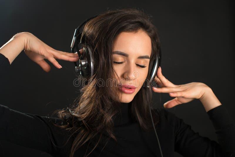 Belle jeune femme appréciante écoutant la musique dans l'écouteur sans fil avec les yeux fermés sur le fond de noir foncé photos libres de droits