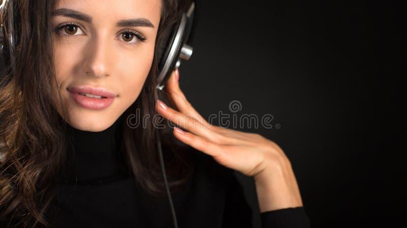 Belle jeune femme appréciante écoutant la musique dans l'écouteur sans fil avec les yeux fermés sur le fond de noir foncé photographie stock libre de droits