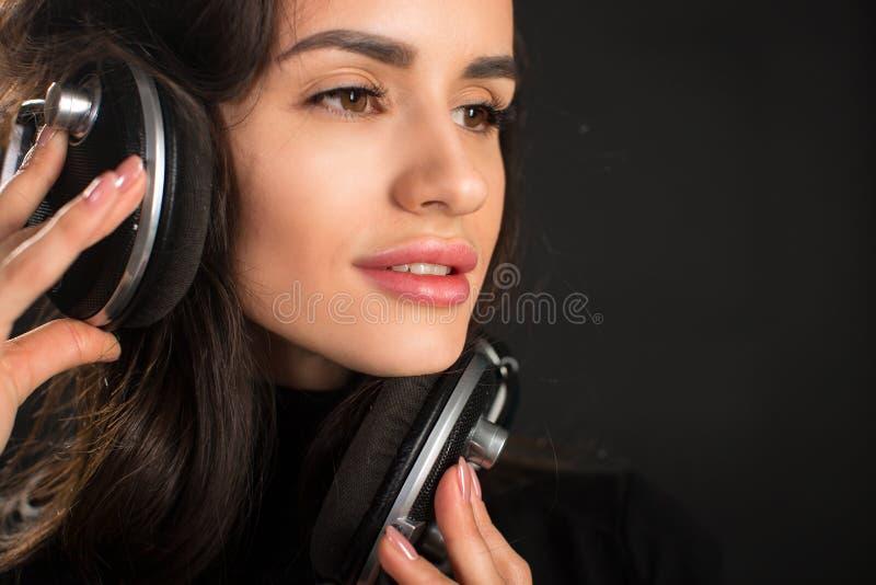 Belle jeune femme appréciante écoutant la musique dans l'écouteur sans fil avec les yeux fermés sur le fond de noir foncé images libres de droits