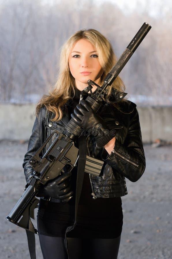 Belle jeune femme armée images stock
