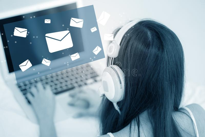 Belle jeune femme asiatique à l'aide d'un clavier d'ordinateur portable avec le téléphone principal d'envoyer l'email photographie stock