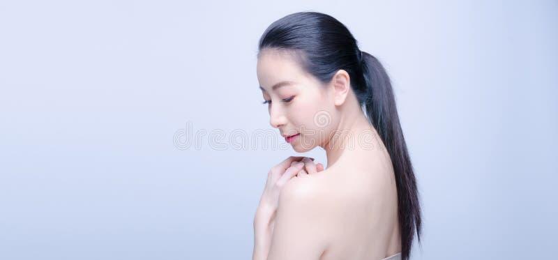 Belle jeune femme asiatique avec la peau fraîche propre dans la vue arrière à coté arrière photos libres de droits