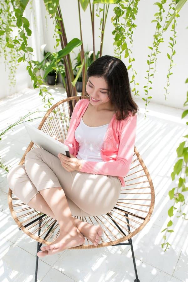 Belle jeune femme asiatique détendant et à l'aide du comprimé numérique image libre de droits