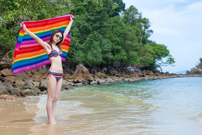 Belle jeune femme asiatique dans le bikini avec le tissu coloré appréciant sur la plage dans des vacances d'été photographie stock