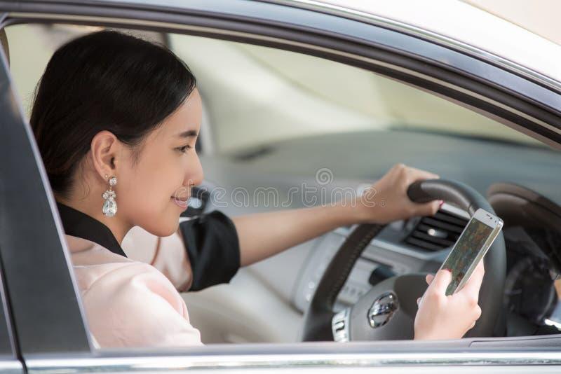 Belle jeune femme asiatique employant la carte dans le mobile dans une voiture image libre de droits