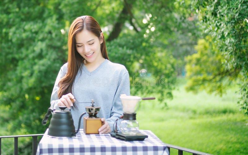 Belle jeune femme asiatique féminine détendant dans l'arrière-cour dans le matin paresseux de week-end avec du café de brassage d photographie stock libre de droits
