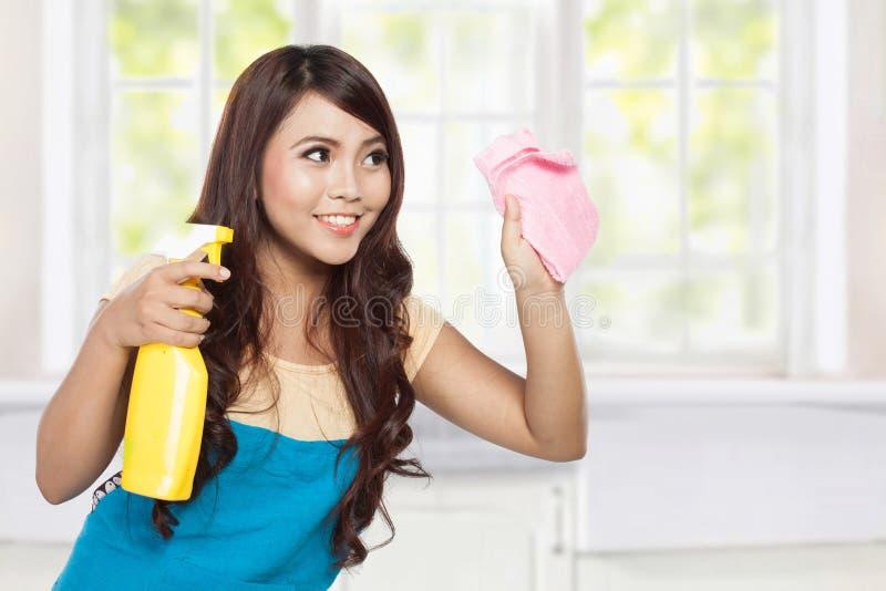 Belle jeune femme asiatique faisant des corvées, tenant le pulvérisateur et le pi photographie stock