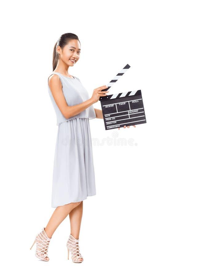 Belle jeune femme asiatique jugeant le panneau de clapet de cinéma d'isolement photo stock
