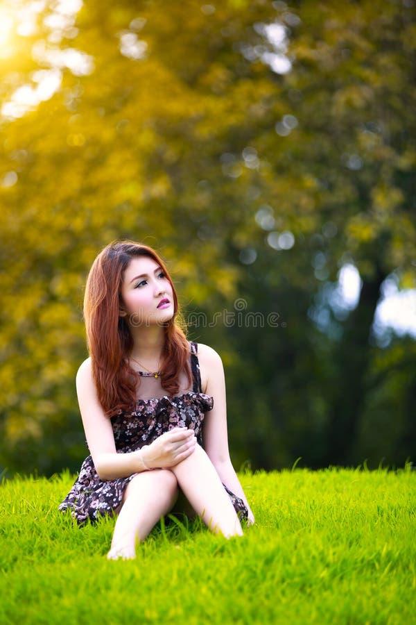 Belle jeune femme asiatique s'asseyant sur l'herbe verte photographie stock libre de droits