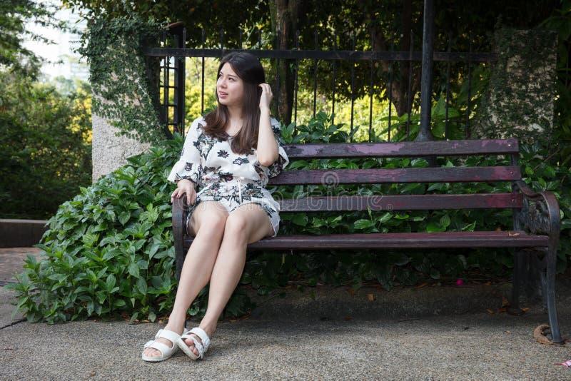 Belle jeune femme asiatique s'asseyant sur le banc dans le jardin extérieur image stock
