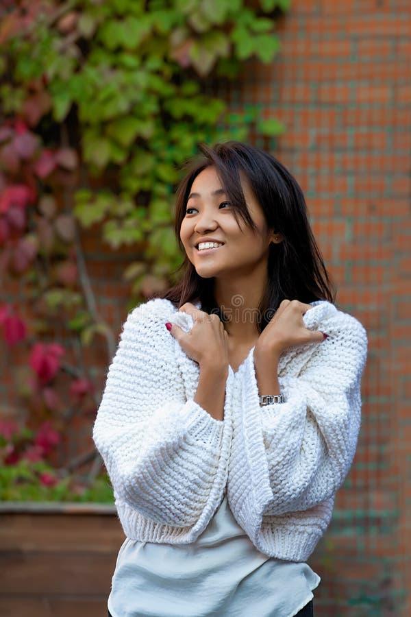 Belle jeune femme asiatique se tenant dans un cardigan chaud pourpre tricoté à côté d'un mur de briques images libres de droits