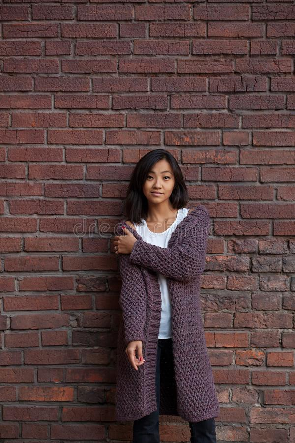 Belle jeune femme asiatique se tenant dans un cardigan chaud pourpre tricoté à côté d'un mur de briques images stock