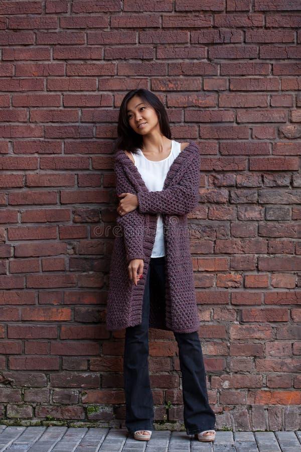 Belle jeune femme asiatique se tenant dans un cardigan chaud pourpre tricoté à côté d'un mur de briques photographie stock